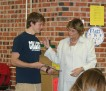 Josh shows Mrs. J his scholarship renewal letter at a luncheon held for the Communicator students.