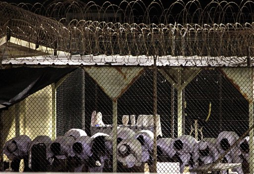 In this photo taken Thursday, May 14, 2009 and reviewed by the U.S. military, Guantanamo detainees pray before dawn near a fence of razor-wire inside the exercise yard at Camp 4 detention facility, at Guantanamo Bay U.S. Naval Base, Cuba. President Barack Obama says he is restarting U.S. military tribunals for the small number of terrorist suspects among all the detainees held at Guantanamo, though with several new legal protections for defendants. (AP Photo/Brennan Linsley)